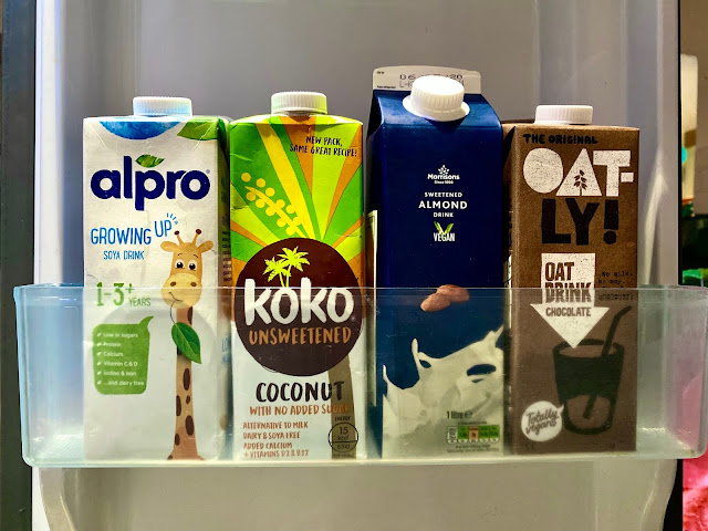 A fridge shelf with: alpro growing up soya drink, Koko unsweetened, Almond drink and oatly chocolate milks