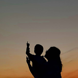 Silhouette of women holding a baby