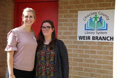 Two women stand next to each other. On the wall behind them, a sign reads, Choctaw County Library System, Weir Branch.