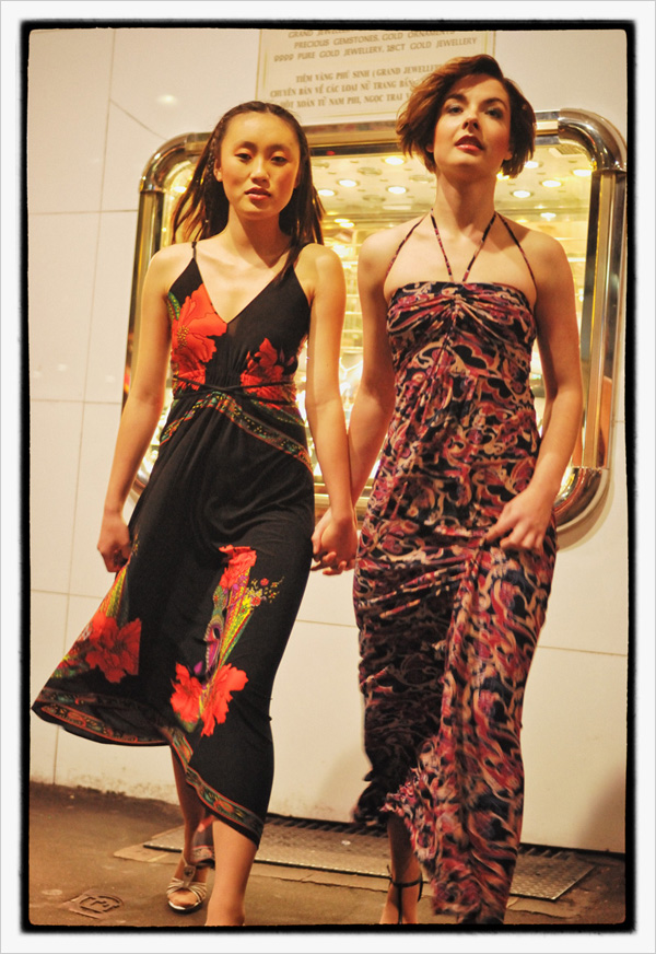 Two mdels stepping across the pavement at night outside a jewellers in Chinatown Sydney, 2007 fashion photoshoot.