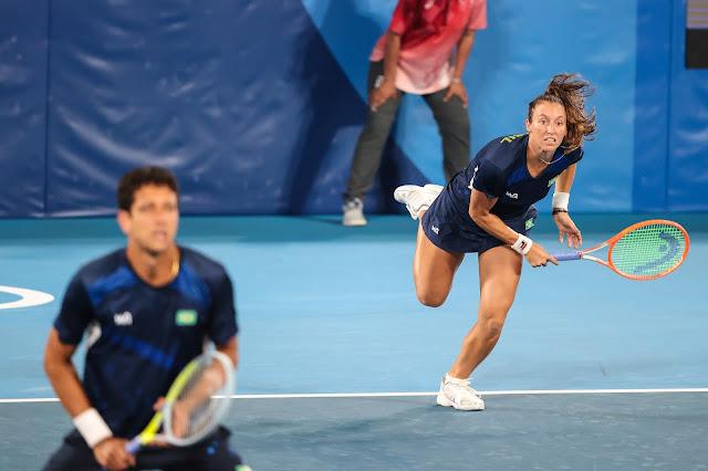 Luisa Stefani efetua um saque, enquanto Marcelo Melo espera o retorno da bola, numa partida de duplas mistas