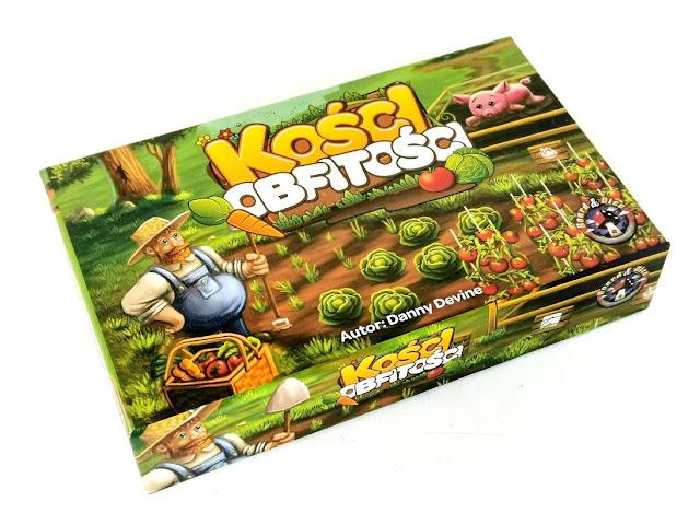 na zdjęciu pudełko gry Kości obfitości a na nim gruby farmer, stojący obok ogródka z marchewkami, sałata i pomidorami