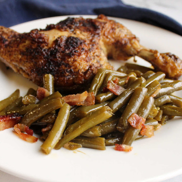 chicken leg quarter and green beans with bacon on plate