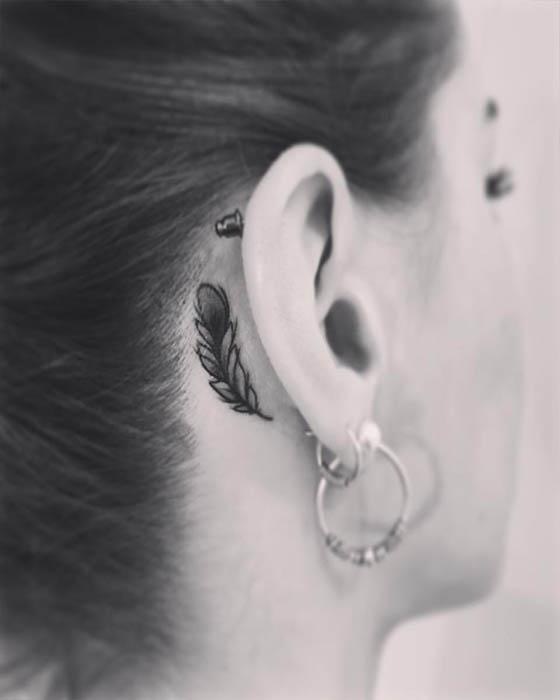 tatuaje detrás oreja pluma