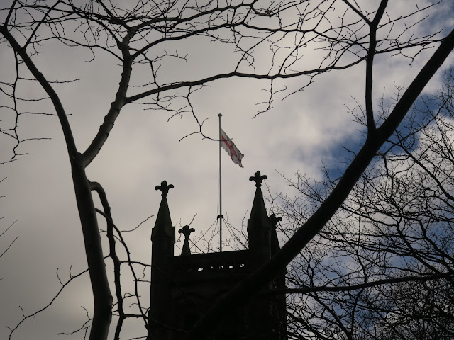 St George's Church Halifax flying St George's flag. Framed with bare branches.