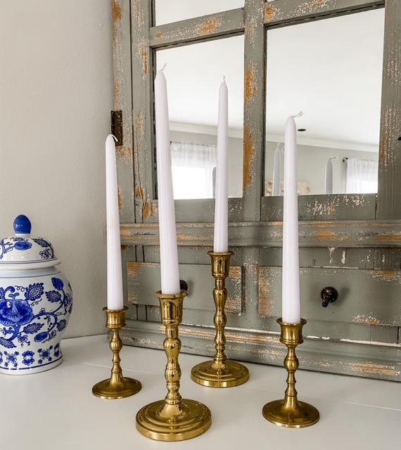 four brass candlesticks white taper candles ginger jar