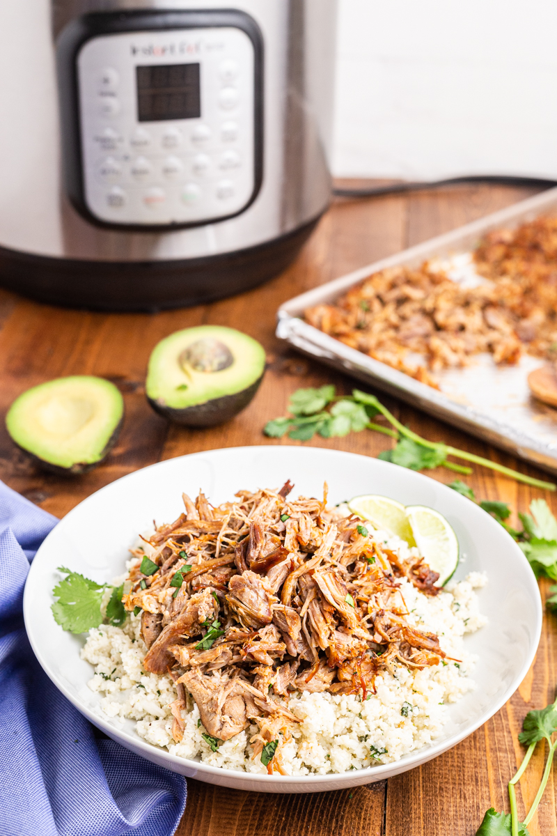 Photo of a burrito bowl made with Easy Keto Pork Carnitas on a wooden table with an Instant Pot in the background.