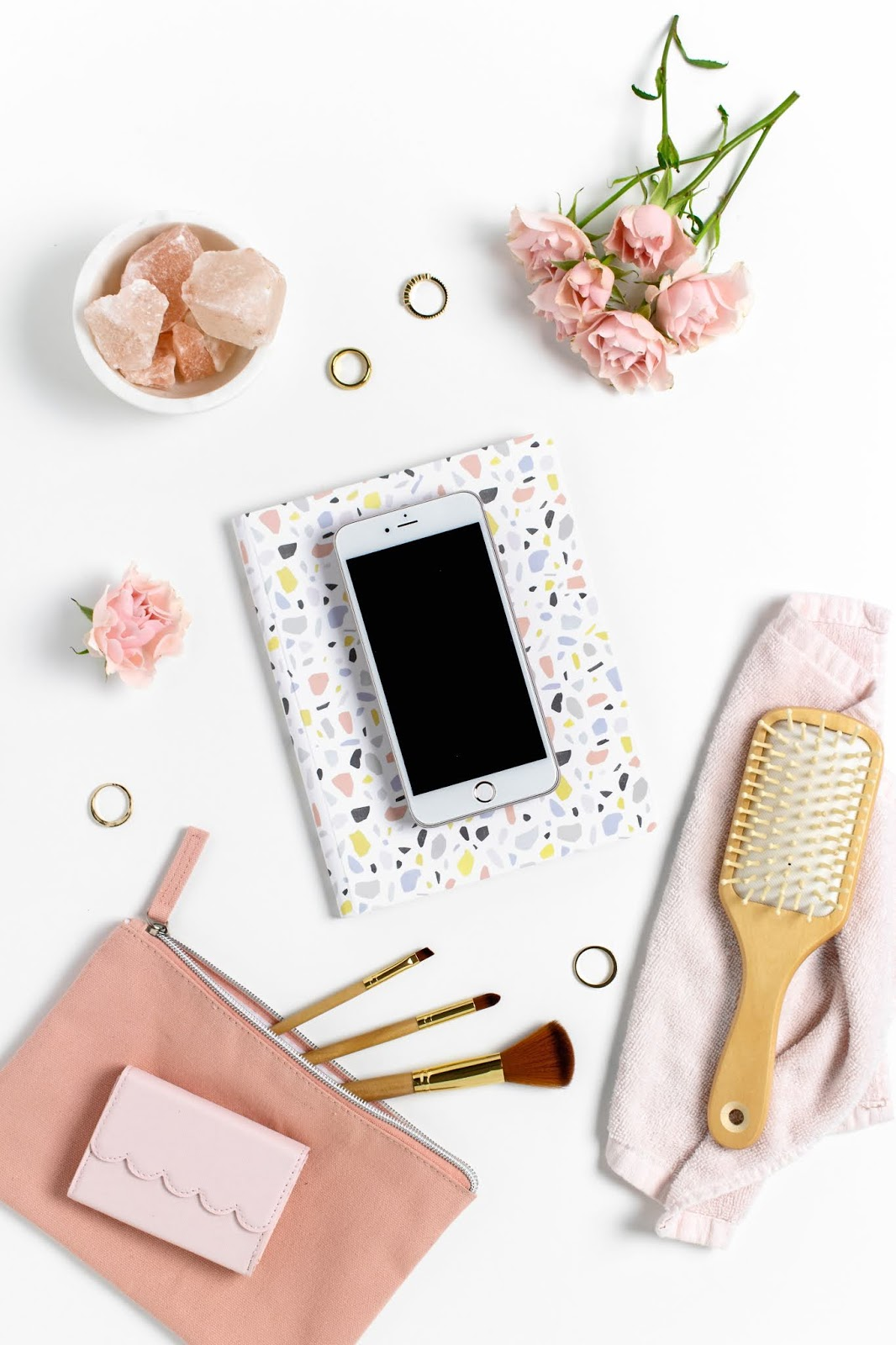 Birds eye view of a phone on a white table with pink flowers and a notebook