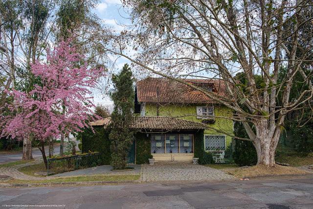Fachada de casa entre árvores, uma delas florida