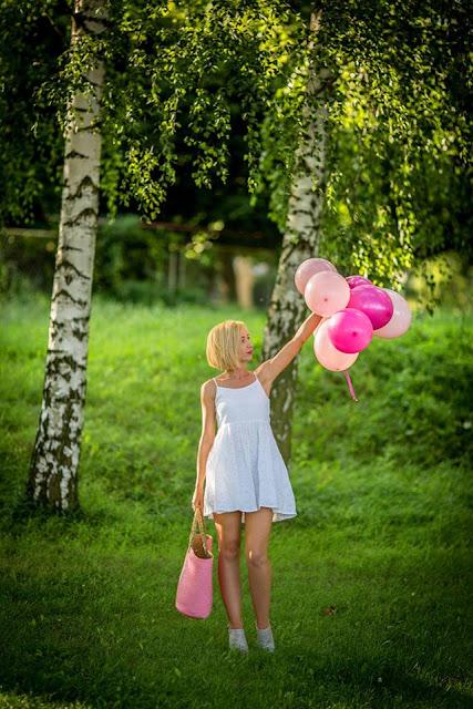 Balony, różowy koszyk z gwiazdą i biała sukienka.