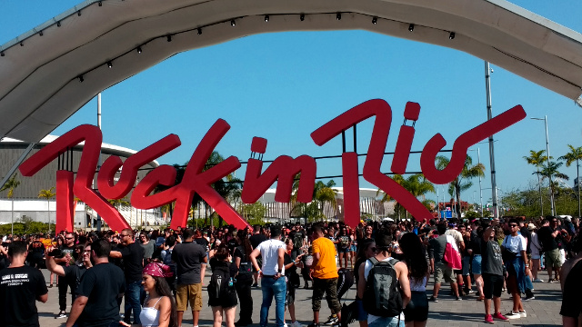 The sign at the entrance of Rock in Rio full of people around trying to take a picture.