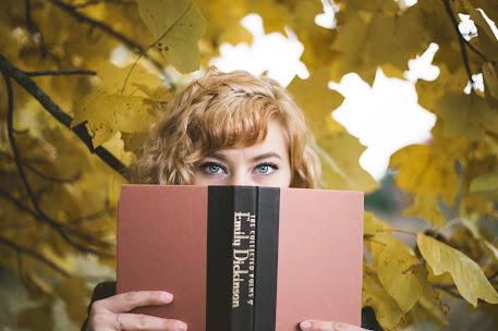 chica con un libro de poesìa cubriendo su rostro