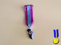 """Medalla zapatilla de correr morada con """"Q"""" del programa"""