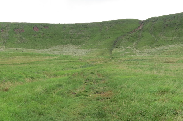 A path heads though grassland to the long ridge on the horizon, which it climbs steeply.