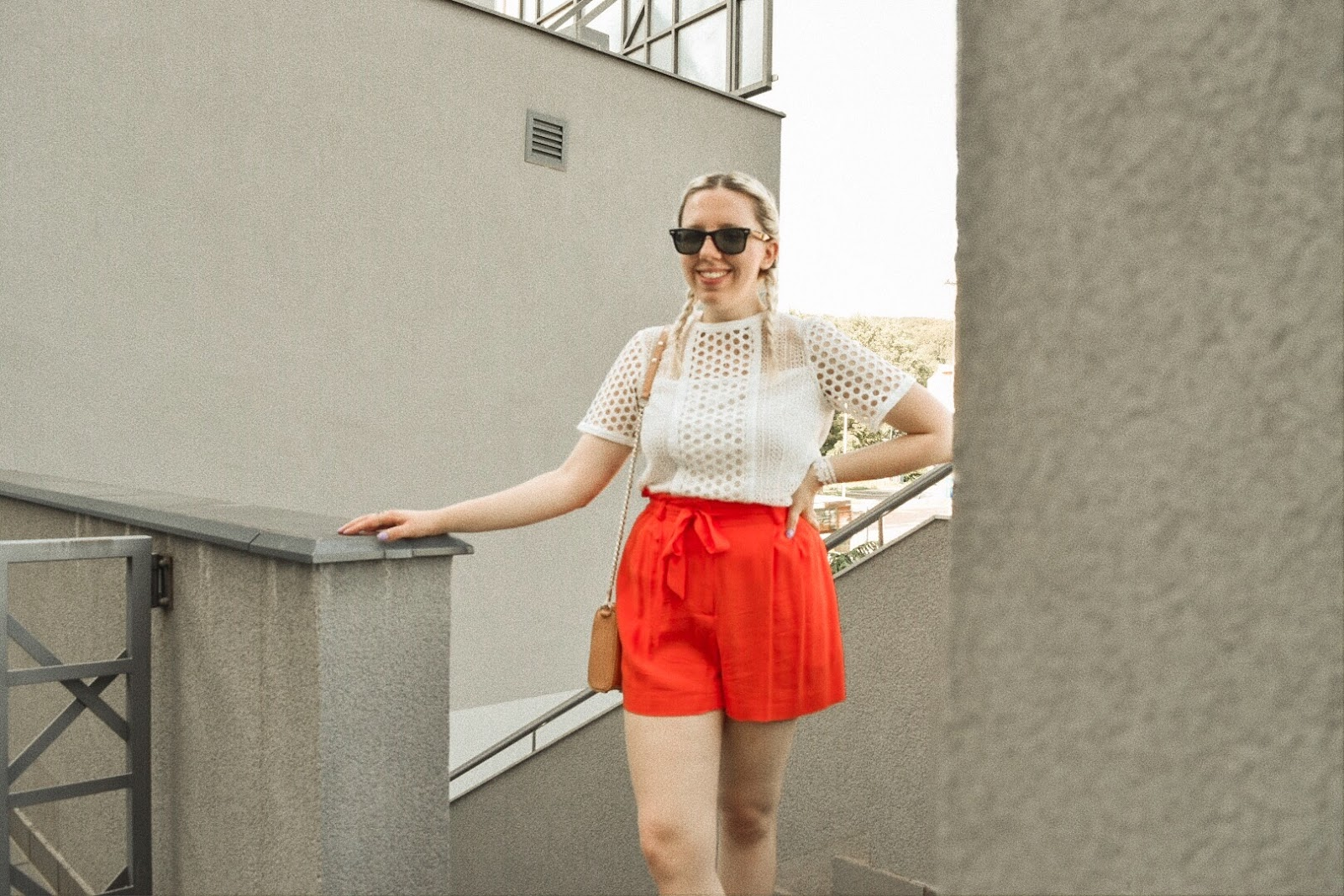 Fashion blogger wearing white top and orange shorts