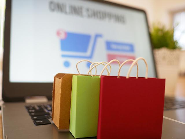 computador ligado e sacolas coloridas na frente