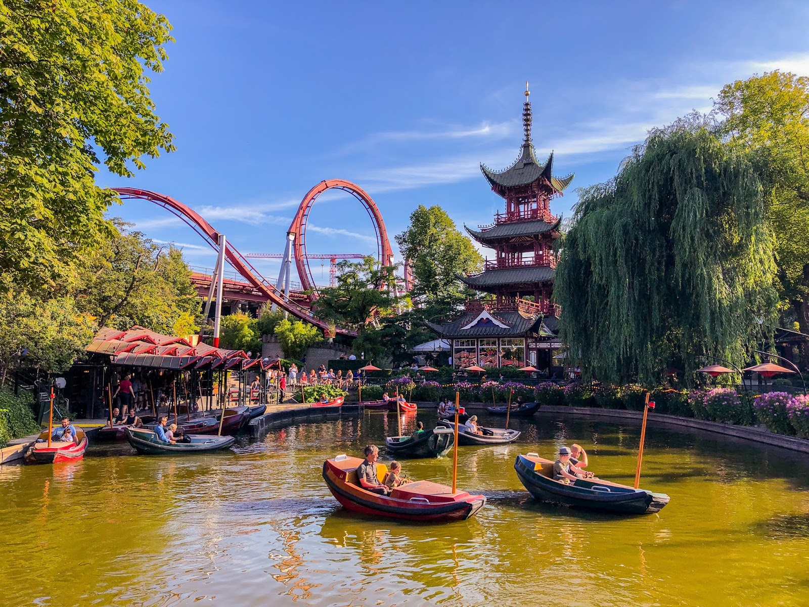 Chinese section of Tivoli amusement park gardens in Copenhagen with traditional Chinese architecture, lake, boats and rollercoaster in background