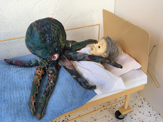 Fabric octopus puppet lying on the chest of a girl puppet in a puppet hospital bed