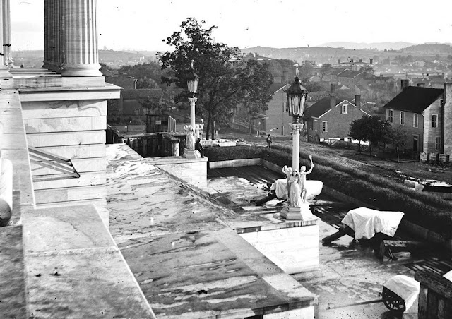On the steps of the Tennessee State Capitol building in Nashville, Tennessee, with covered guns (lower right) set up nearby, in 1864.