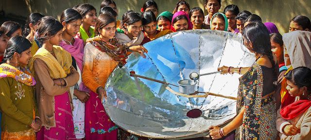 En la India, una mujer demuestra como cocinar con un reflector solar.UNDP India