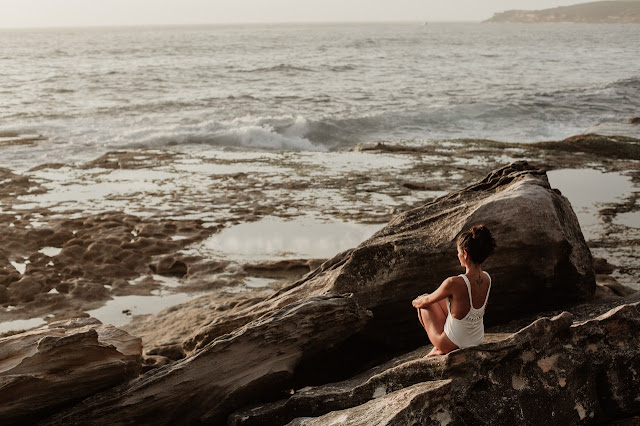 A women practising focus and self-control while sitting on rocks and looking out towards the sea