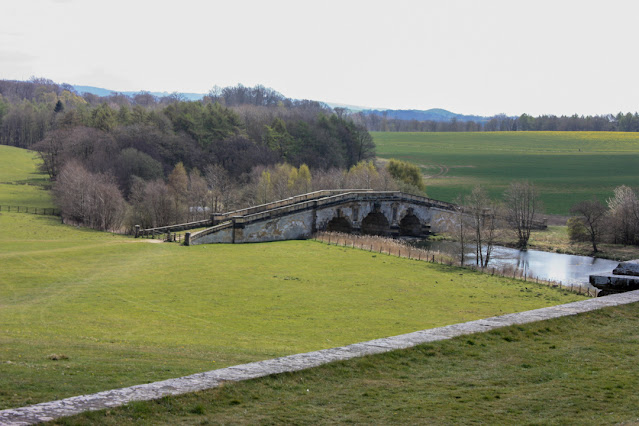 Traditional Yorkshire countryside with rolling green hills, trees and a magnificent stone bridge.