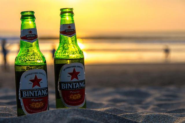 Menikmati bir di Pantai Kuta