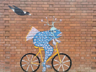 Fish riding bicycle mural in Dickson, ACT by Bev Hogg
