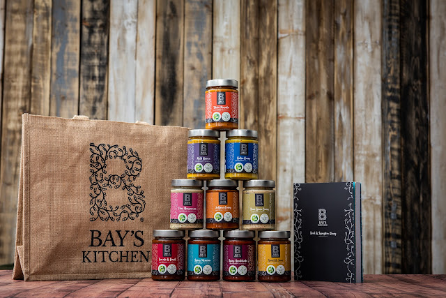 There is a burlap tote bag to the left of the image with Bay's kitchen logo on. Next to the bay is a pyramid of jars. The jars are all of Bay's Kitchen range