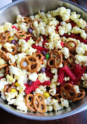 Big mixing bowl full of popcorn, pretzels and candy for snack mix
