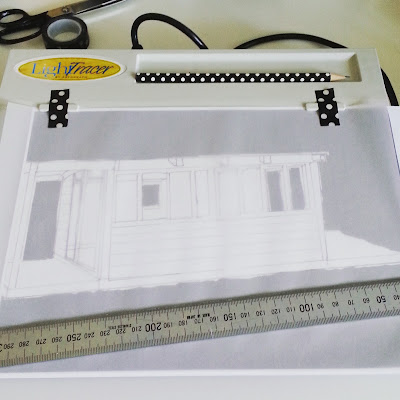 Lightbox with a sketch of a holiday house and a sheet of tracing paper on top.
