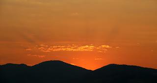 Sunbeams burst above the ridge