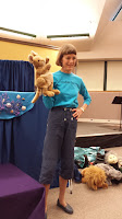 Woman stands with kangaroo puppet on right hand, left hand on hip, smiling out at crowd.
