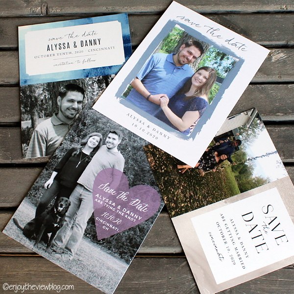 Four different personalized save-the-date cards lying on a wooden table