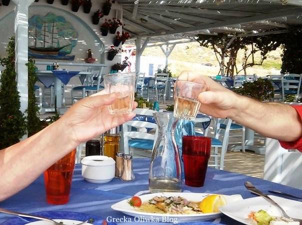 toast szklaneczkami wina w greckiej tawernie na stole grillowane owoce morza obok cytryna oraz pomidor