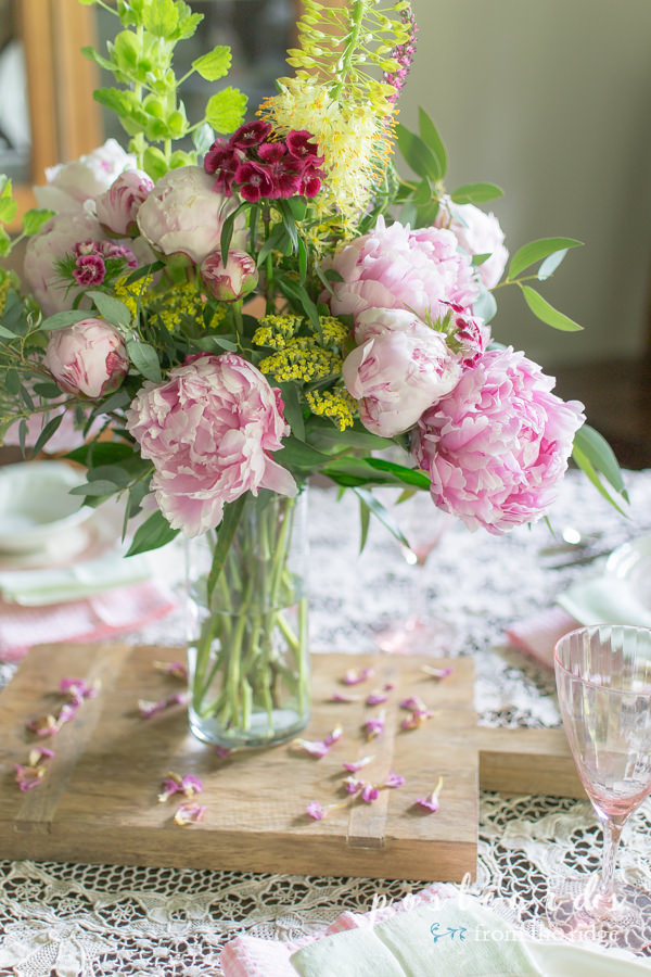 pink peony centerpiece on wood cutting board