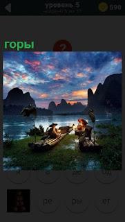 На фоне гор находится озеро и на берегу расположились лодки и рыбаки
