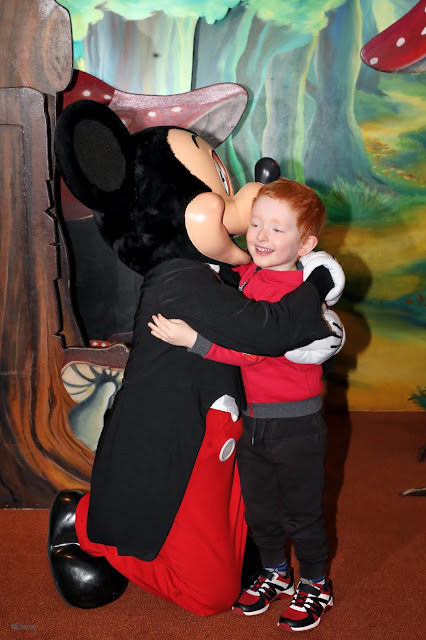 Little boy hugging Mickey Mouse