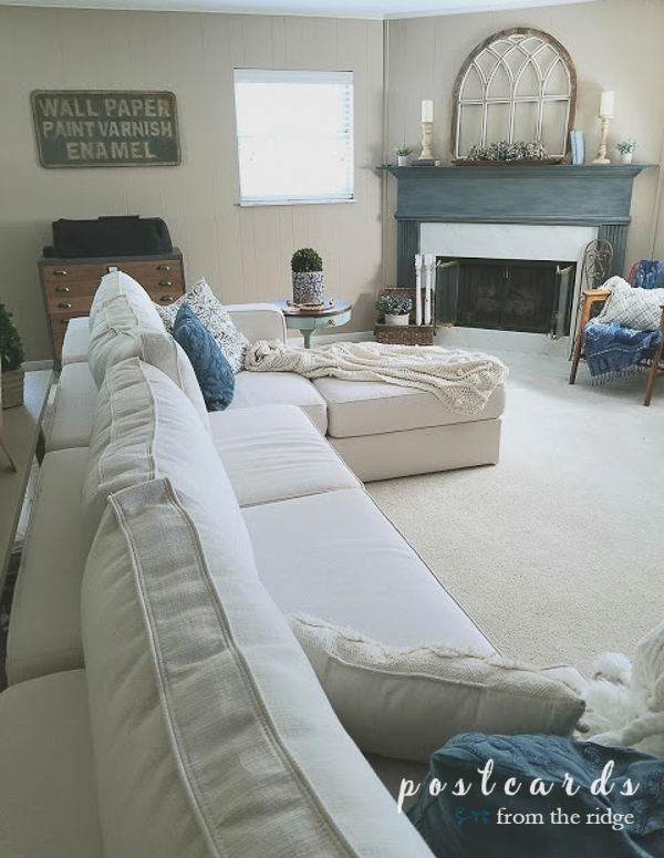 large white love sac sectional sofa with blue accents in family room