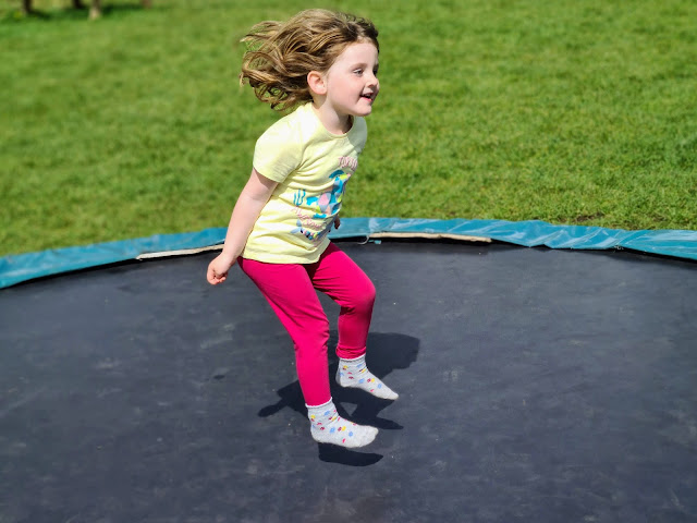 Image taken at Tattershall Farm Park of a child jumping on an in ground trampoline.