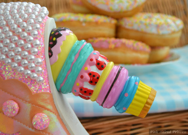 macaron cake doughnut heel in front of doughnuts and picnic basket