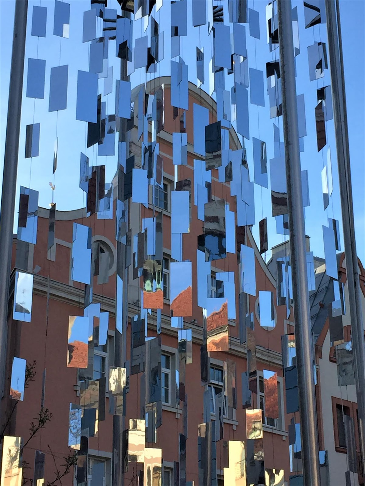 Un palazzo della città vecchia attraverso uno scultura di specchi