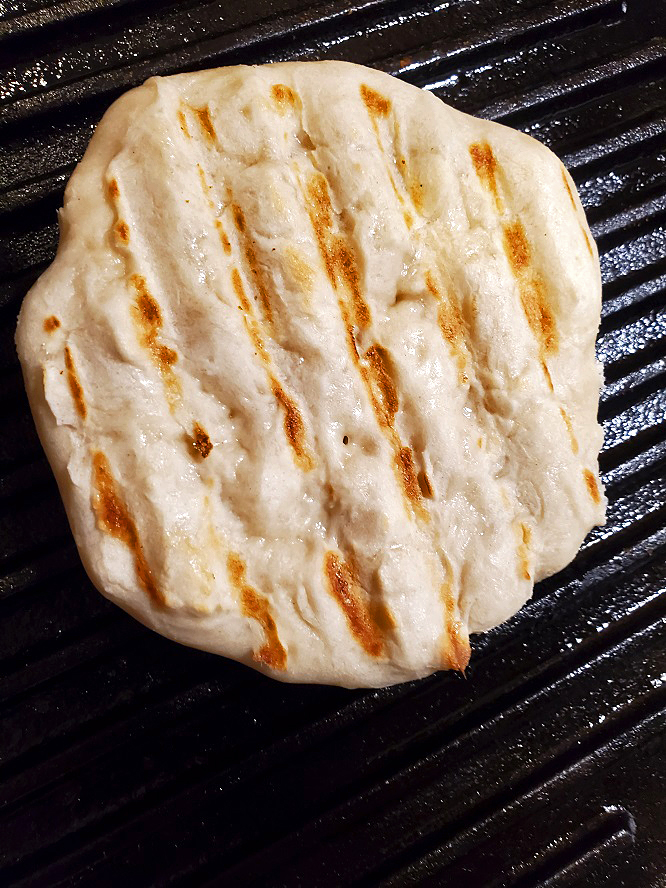 this is pita bread cooking in a cast iron skillet