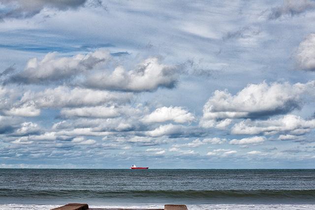 HDR.barco en el horizonte con cielo nuboso.