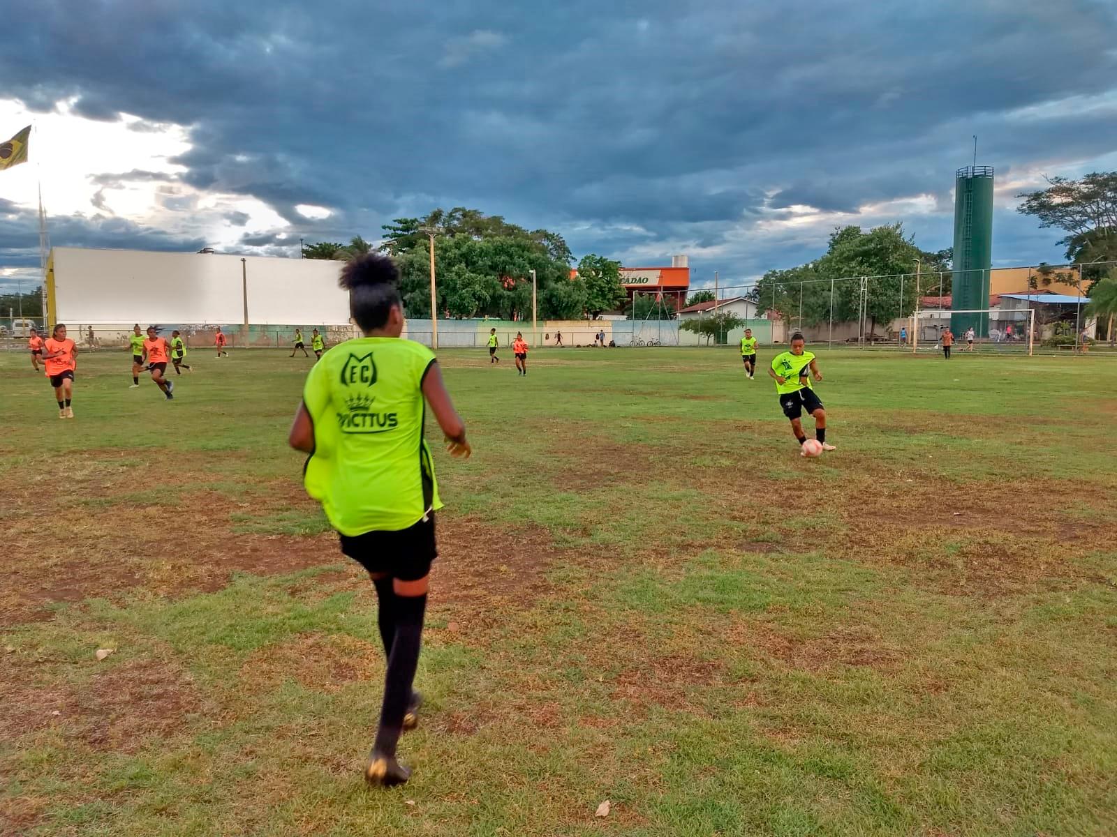 Meninas jogam futebol feminino no campo