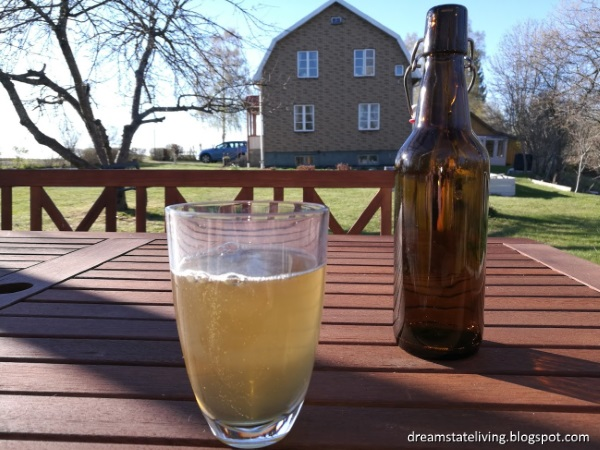 photo of home made apple cider in a glass with bottle in background and house even further back