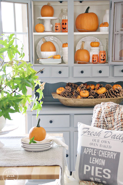 dough bowl full of pumpkins and pinecones, hutch with white china and orange pumpkin arrengement, fresh daily pillow