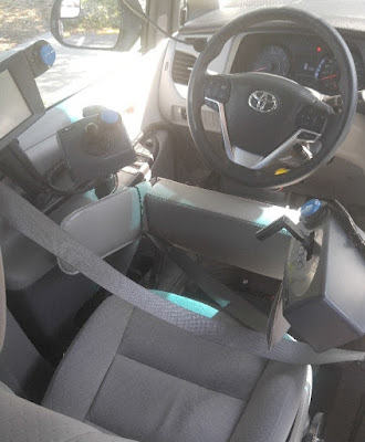 An image of a vehicle and high tech, adaptive driving solutions. Behind the steering wheel, a joystick is located on the left side and a throttle mechanism is located on the right