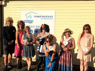 Miss Harjuranta -kilpailun osanottajat ja juontajakaksikko ryhmäkuvassa Kylätuvan edustalla.