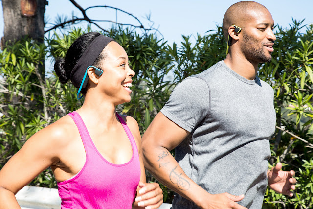 Runners wearing AfterShokz Titanium Trekz wireless open ear headphones